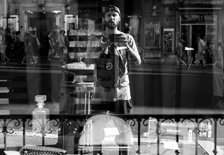 Young man reflecting on glass window while photographing outside store