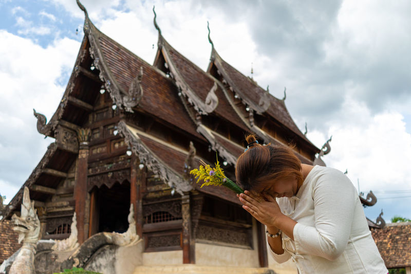 Woman praying while standing against temple