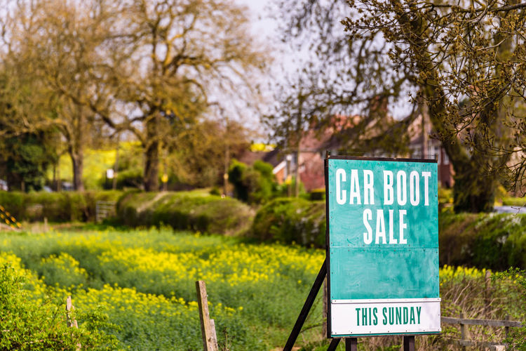 Car boot sale This Sunday sign with field on bachground Communication Day Flower Focus On Foreground Grass Green Color Growth Information Information Sign Land Nature No People Outdoors Park - Man Made Space Plant Sign Text Tree Warning Sign Western Script