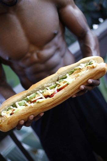Midsection Of Shirtless Man Holding Hot Dog While Standing In Gym