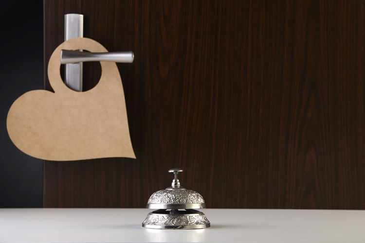 Close-up of electric lamp on table against wall