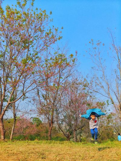 Portrait of boy running on land against trees