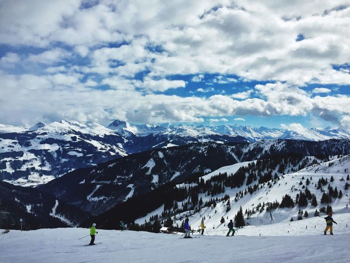 People Skiing On Snow Against Mountains