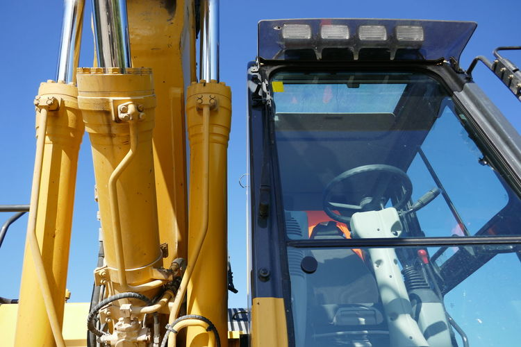 Low angle view of earth mover against sky