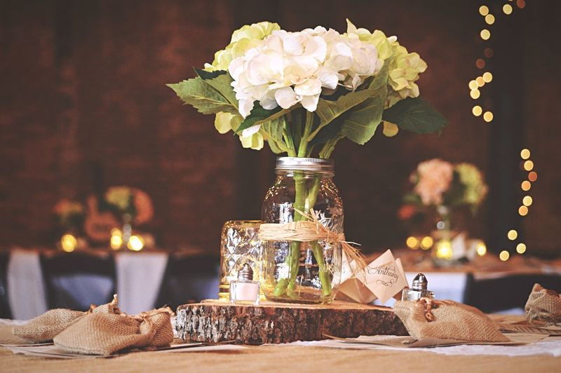 White Flowers In Jar On Tree Stump In Wedding