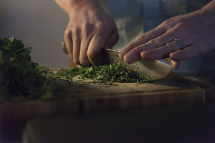 Close up view of a home chef chopping herbs on a wooden cutting board low light. Authentic Moments Basel Cooking Hands Herbs Home Knife Low Light Man Married Authentic Chef Close Up Cutting Board Fingers Food Greens Kitchen Motion Organic Parsley Premium Collection Preparation  Skills  Wedding Ring