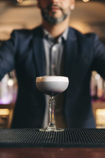 Male bartender with cocktail at bar counter
