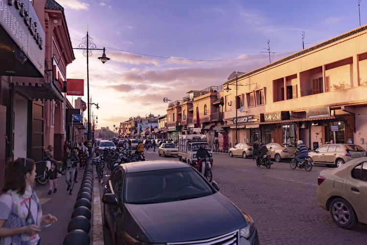 Architecture Building Built Structure Marrakech Marrakesh Morocco Marrakech Morocco Light Light And Shadow City Building Exterior Transportation Street Car Sky Cloud - Sky Road Crowd Pink Sky Purple Sky Busy Street Golden Hour Sunset Cars Motorbikes