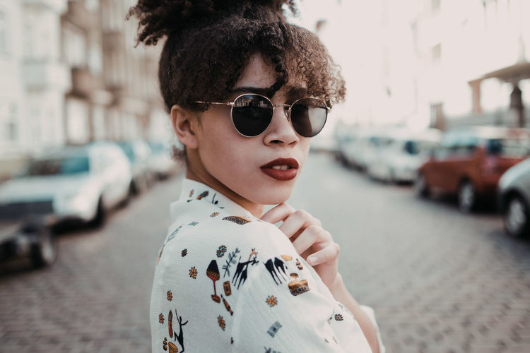 Portrait of young woman wearing sunglasses standing on street in city