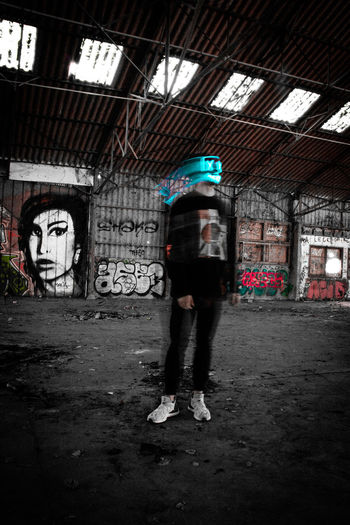 Full length rear view of man standing in abandoned building