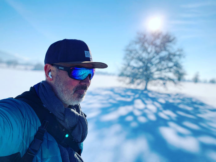 Man wearing sunglasses against sky during winter