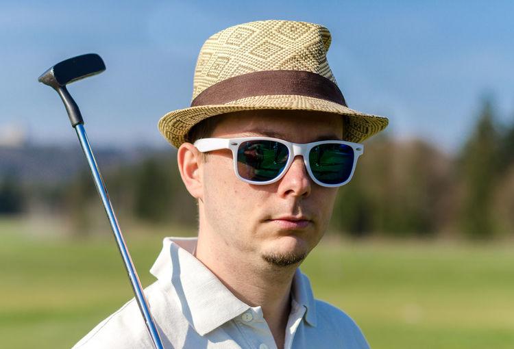 Portrait of man wearing sunglasses holding golf club standing on field