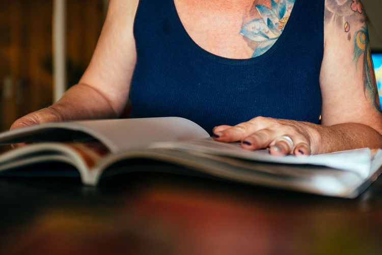 Midsection Of Woman Reading Magazine