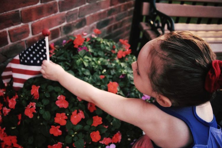 Close-up of girl holding american flag by plants