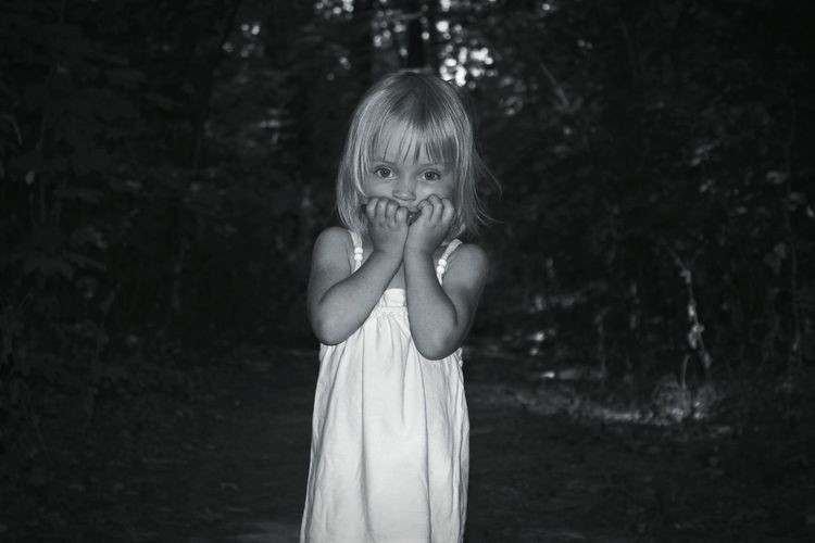 Portrait Of Cute Girl Covering Her Mouth In Forest