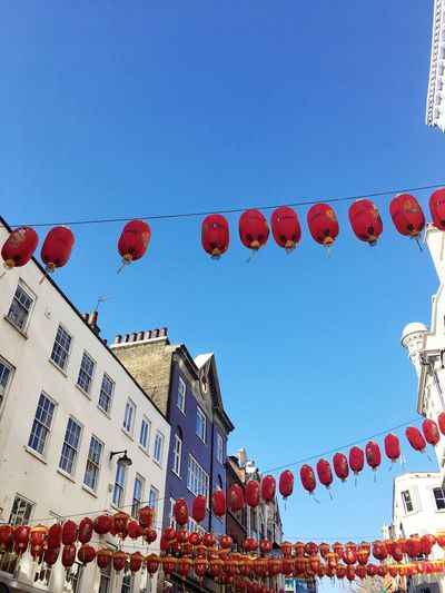Low angle view of lanterns hanging against clear sky