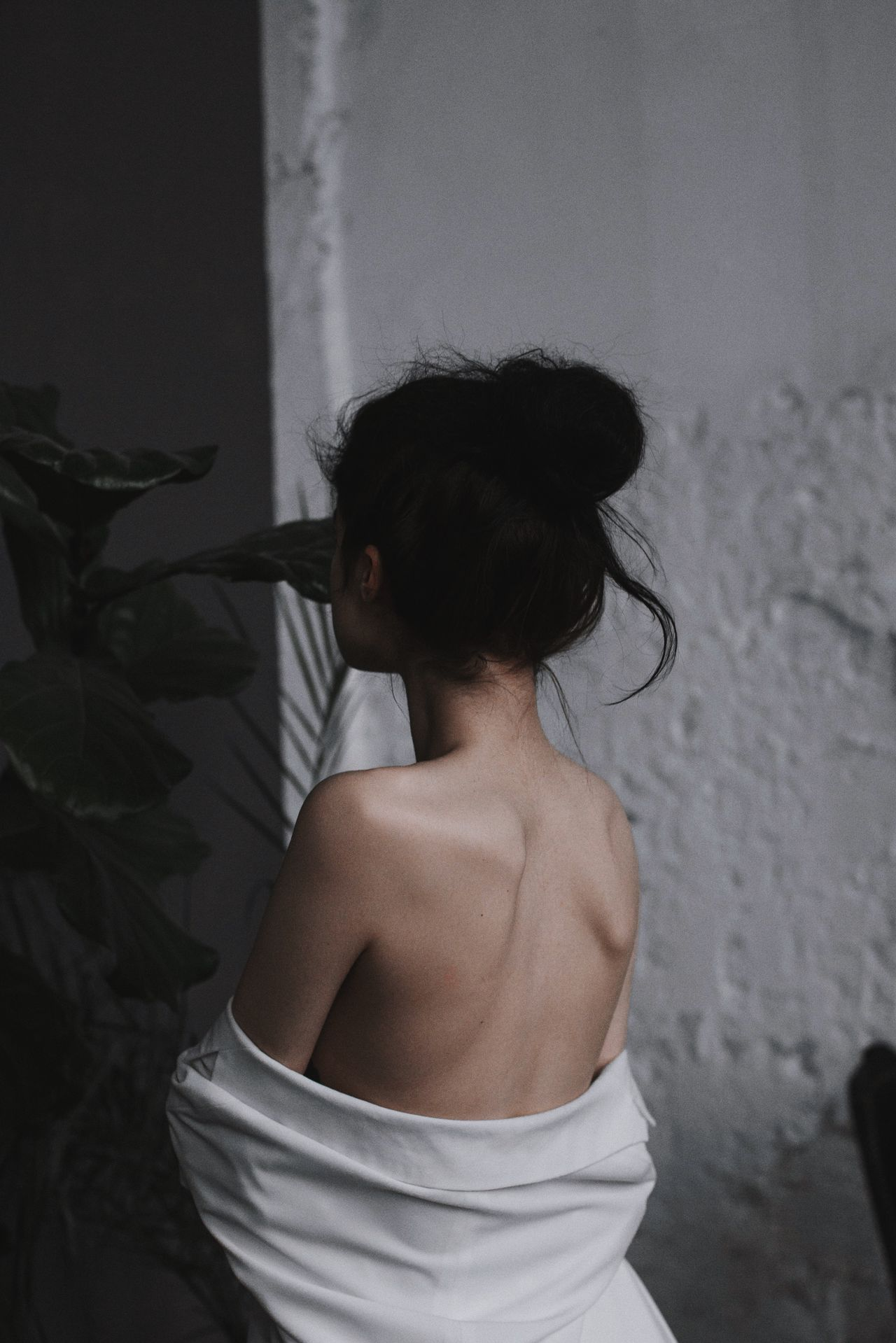 Rear view of shirtless woman standing against wall at home