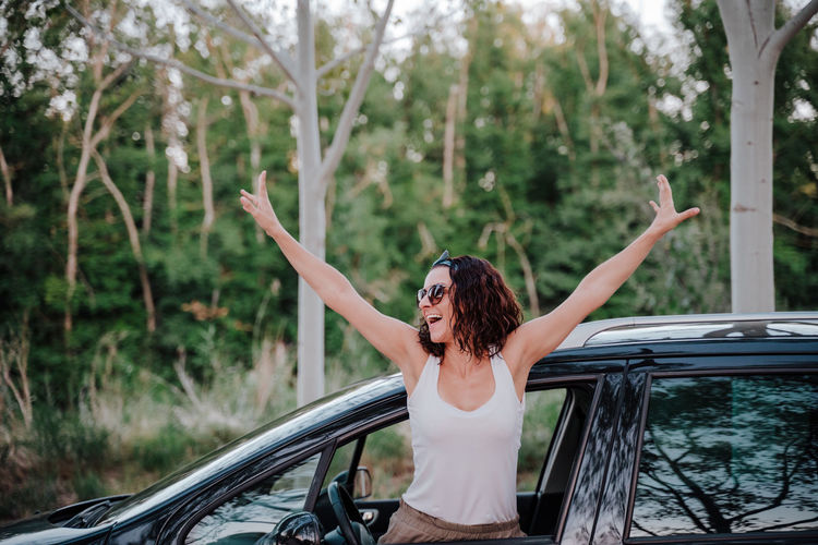 Woman standing in car against tree