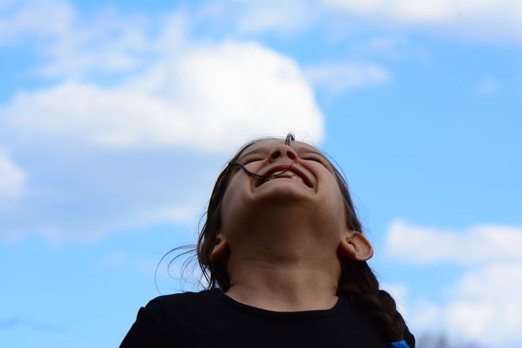 Low angle portrait of girl against sky