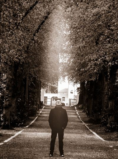 Rear view of man standing on footpath amidst street