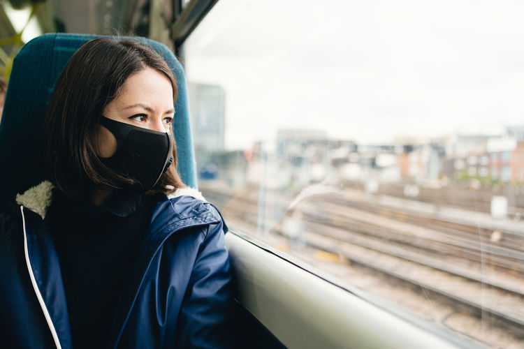 Portrait of beautiful young woman in train wearing a face mask