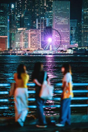 People on illuminated cityscape at night