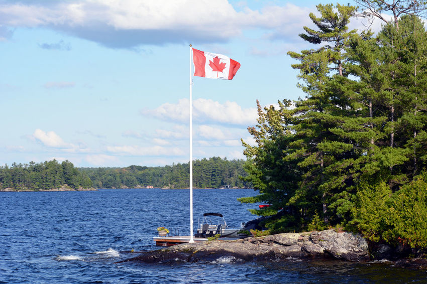 Calm Canadian Flag Cloud - Sky Day Flag Flag Pole Fluttering Green Color Identity In Front Of Lake View National Flag No People Non-urban Scene Outdoors Patriotism Pride Scenics Sky Tranquil Scene Tranquility Tree Water Waterfront Waving