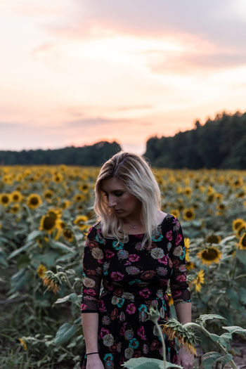 Woman amidst sunflowers on field against sky during sunset