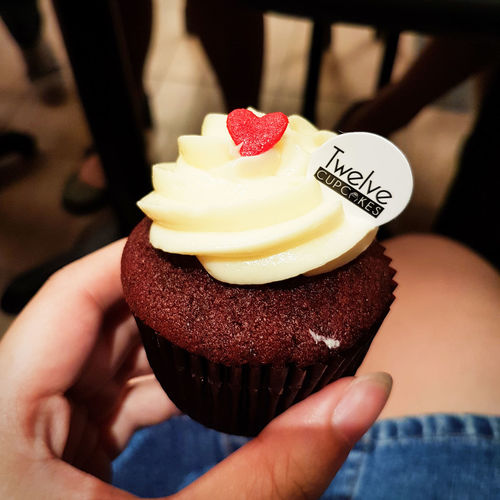A treat Enjoy The New Normal Close-up Day Dessert Food Food And Drink Freshness Holding Human Body Part Human Hand Indoors  Indulgence Maximum Closeness One Person People Ready-to-eat Real People Sweet Food Temptation Treat Twelve Cupcakes Twelvecupcakes Cupcake Treats Redvelvet
