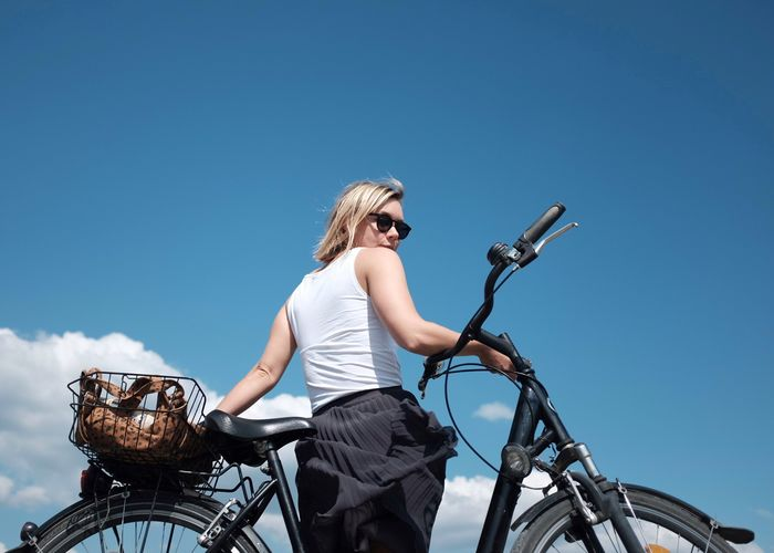 Rear view of woman with bicycle against blue sky