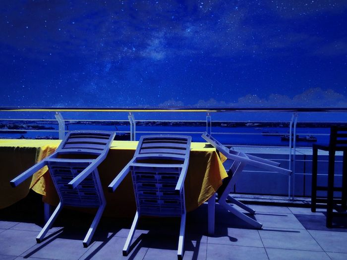Furniture at observation point against sky at night