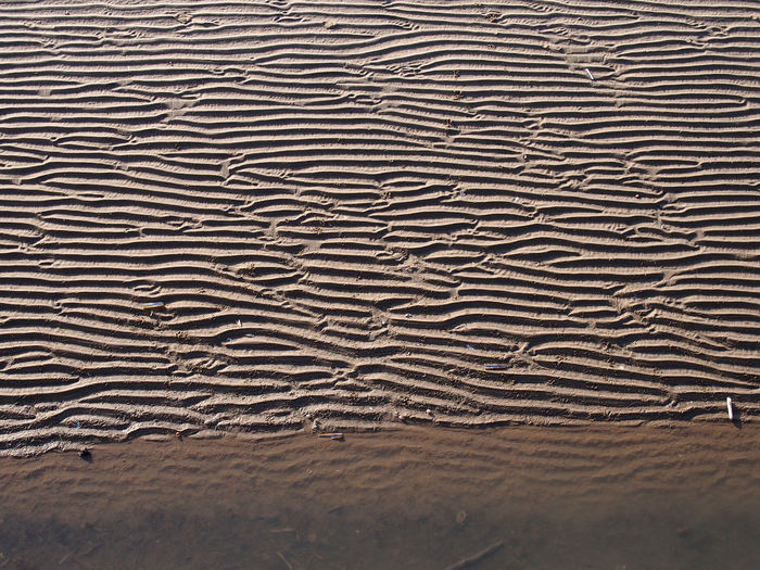 Beach background with wavy pattered surface on wet sand and shadow at the edge of the sea