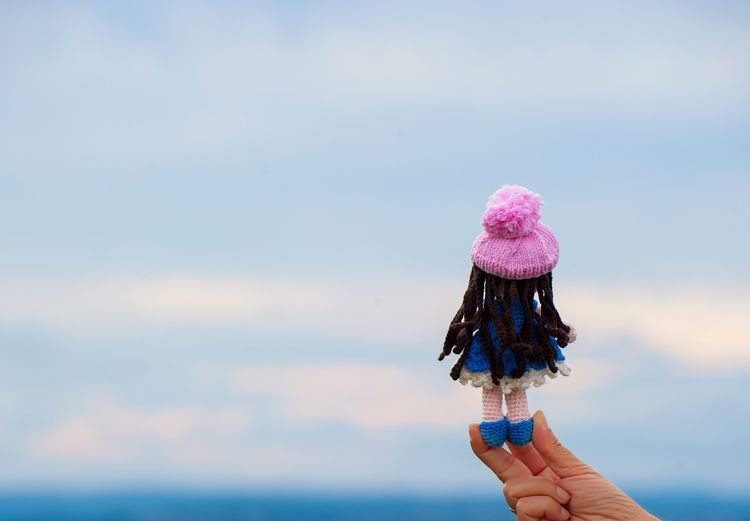 Cropped Hand Of Woman Holding Doll By Sea Against Cloudy Sky