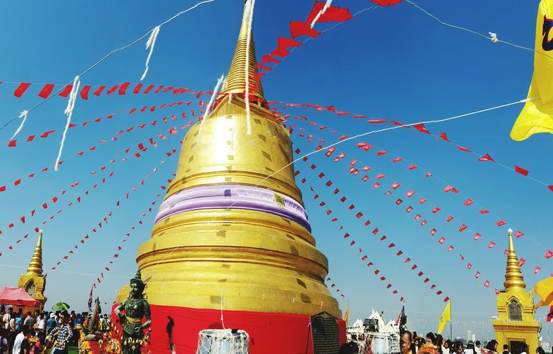 Low angle view of decorated stupas against sky
