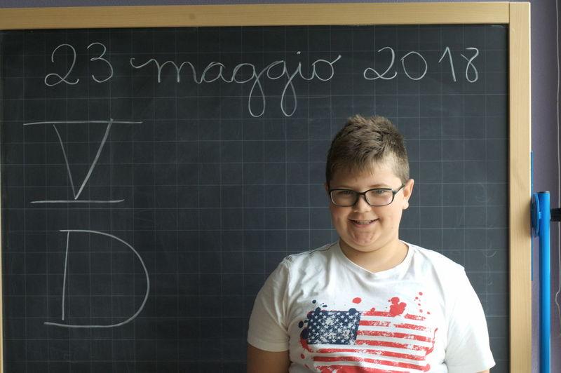 Portrait Of Smiling Student Standing Against Blackboard