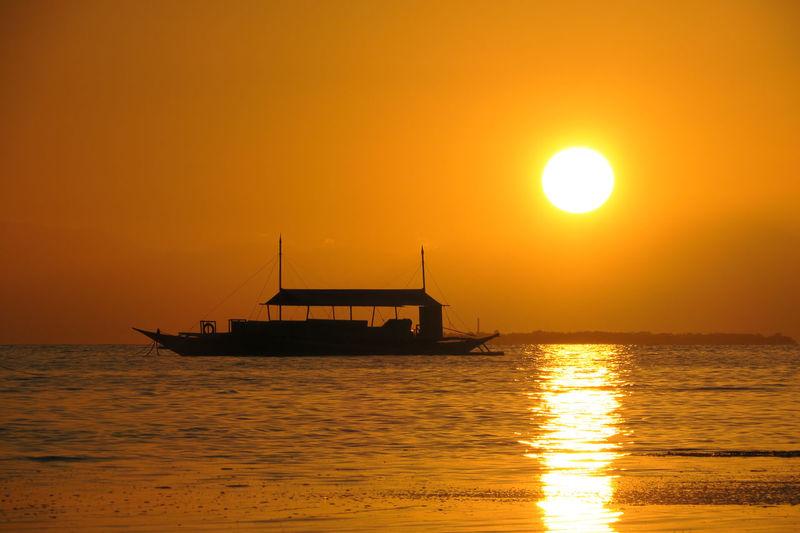 Silhouette ship in sea against orange sky