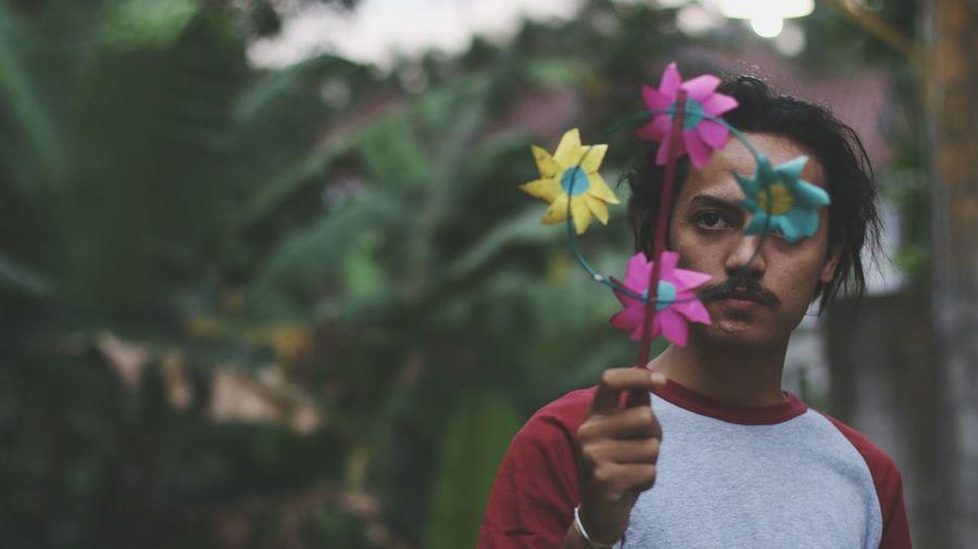 Serious man holding pinwheel toy