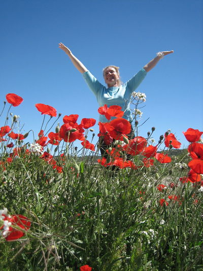 Low angle view of man jumping flower against clear sky