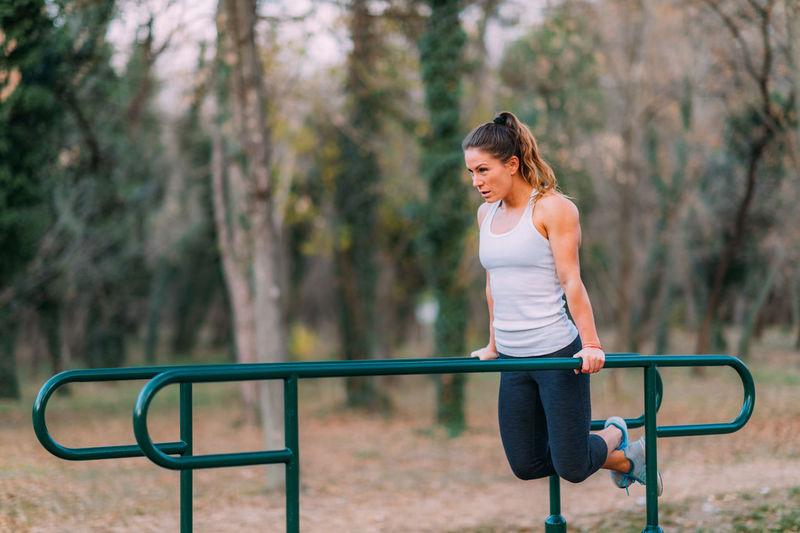 Full length of woman exercising on bars in park