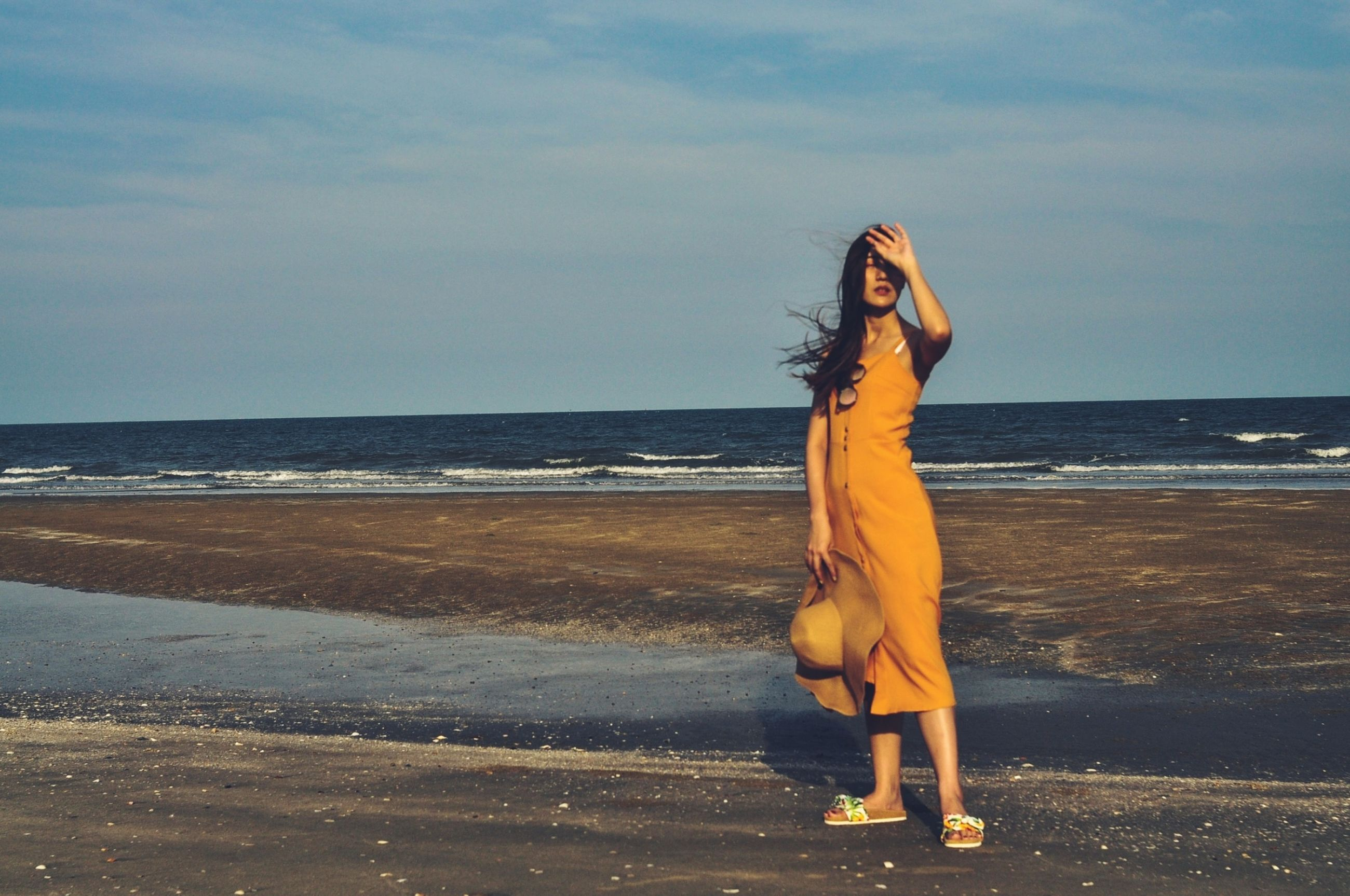 sea, beach, water, land, one person, sky, horizon over water, adult, full length, nature, women, horizon, ocean, long hair, young adult, clothing, standing, beauty in nature, hairstyle, sunlight, shore, leisure activity, fashion, vacation, sand, dress, blue, morning, holiday, lifestyles, trip, motion, coast, tranquility, outdoors, day, person, scenics - nature, wave, walking, cloud, female, body of water, casual clothing