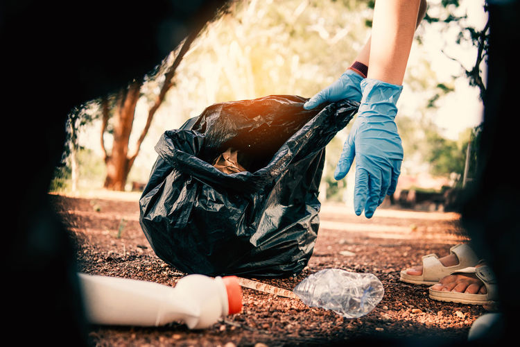 Volunteer holding plastic garbage clean to dispose of waste properly.