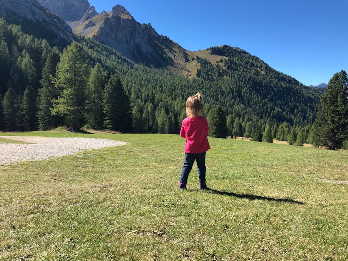 Rear view of girl standing against mountain
