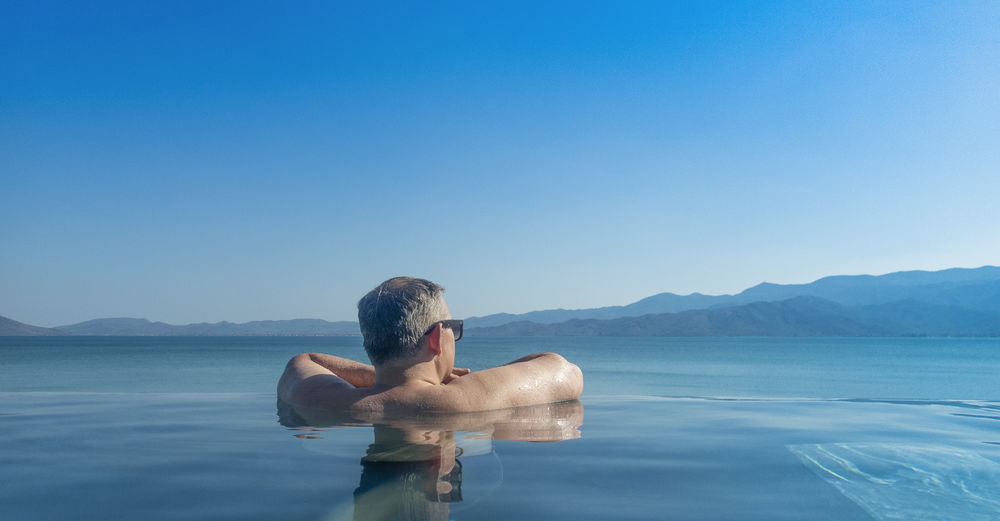Rear view of shirtless man in infinity pool against clear blue sky