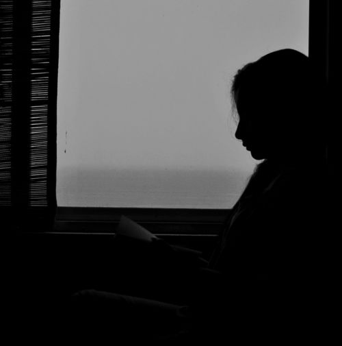 Side view of silhouette woman reading books in house