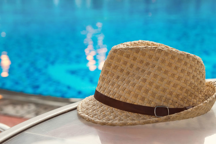 Hat Swimming Pool Pool Water Focus On Foreground Sun Hat Close-up Day Still Life Poolside Clothing Nature No People Straw Hat Fashion Blue Sunlight Glasses Outdoors Personal Accessory Turquoise Colored Vacation Copy Space