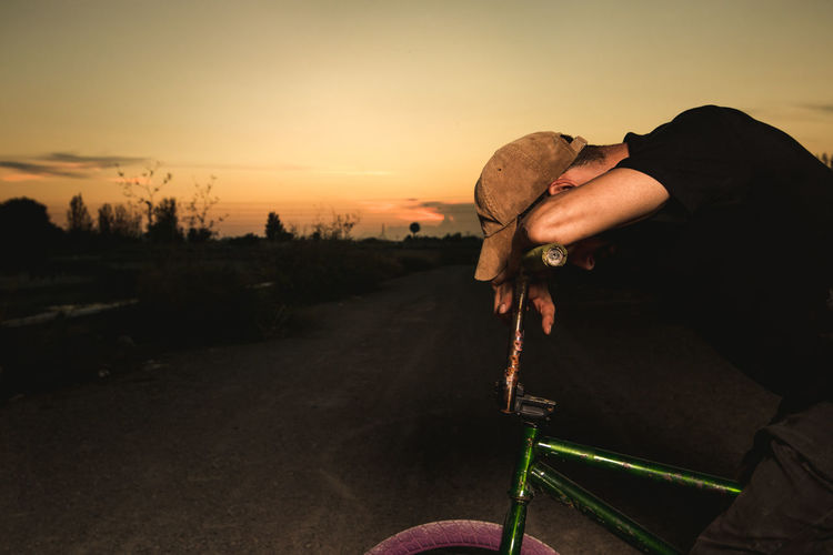 Side View Of Young Man With Bicycle Sitting On Road Against Sky During Sunset