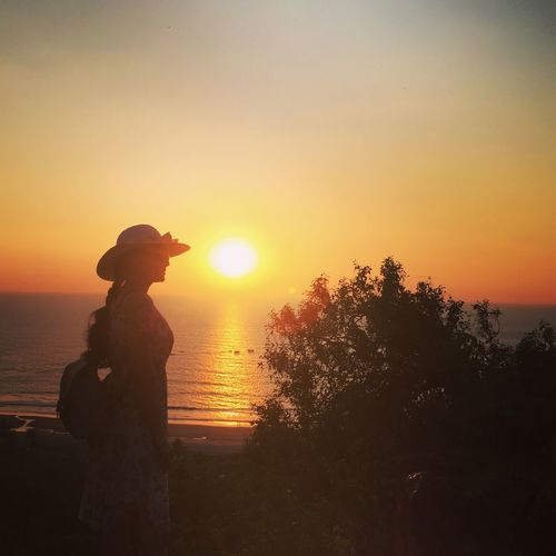 Silhouette person standing by sea against sky during sunset