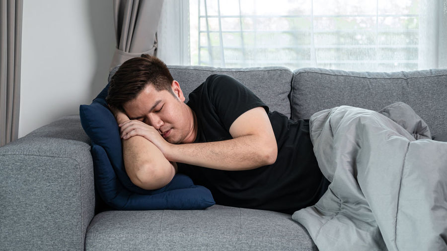 Young man lying down on sofa at home