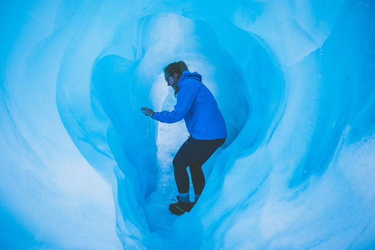 Side view of woman standing in ice cave
