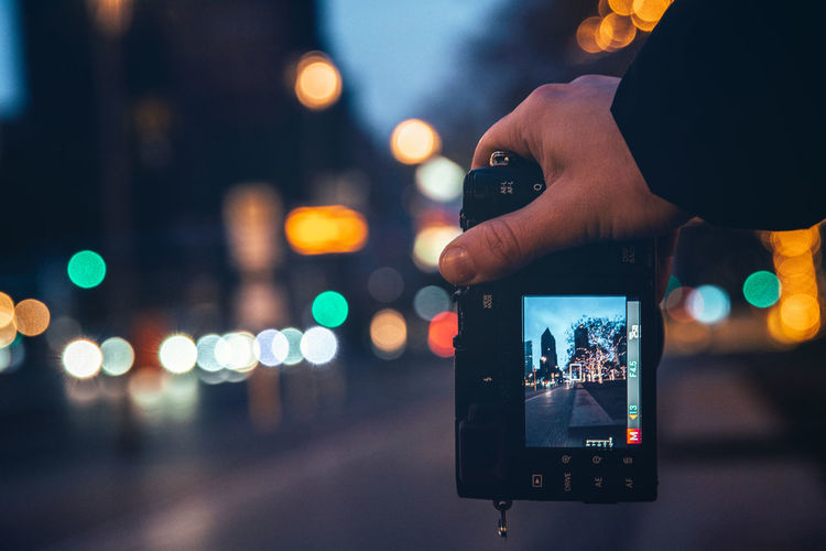Person photographing illuminated smart phone at night
